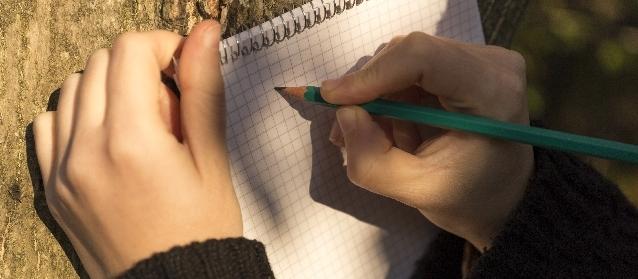 ノートに鉛筆で書き込もうとしています。